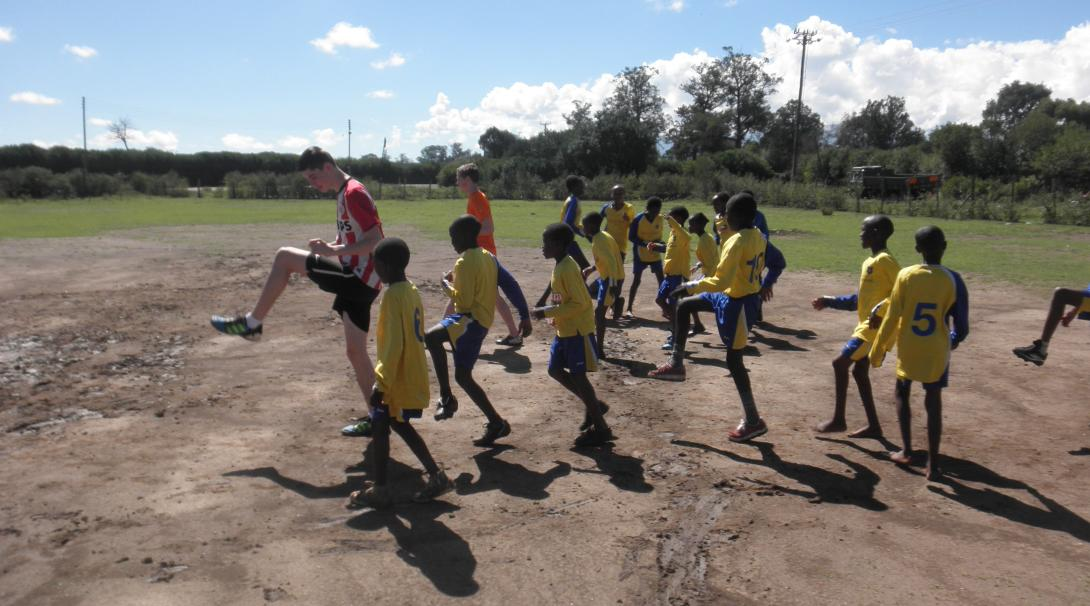 A couple of Projects Abroad volunteers doing their Sports Coaching internship in Kenya run training sessions with children.